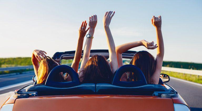 Drei junge Frauen fahren im Sommer glücklich in einem orangenen Cabrio mit offenem Dach und strecken dabei die Arme in die Luft.