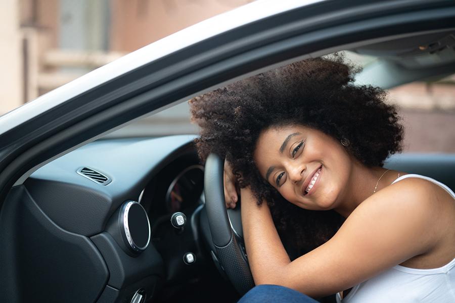 Junge Afroamerikanerin beugt sich über das Lenkrad Ihres Autos und lächelt in die Kamera.