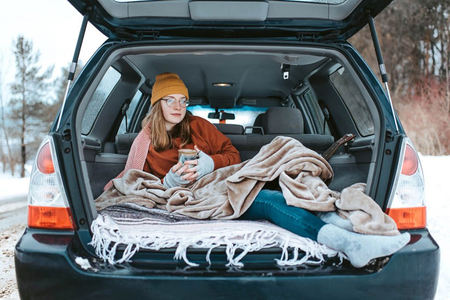 Eine Frau sitzt im Winter warm eingepackt mit Decke in einem geöffneten Kofferraum eines Kombis und hält ein warmes Getränk in der Hand.