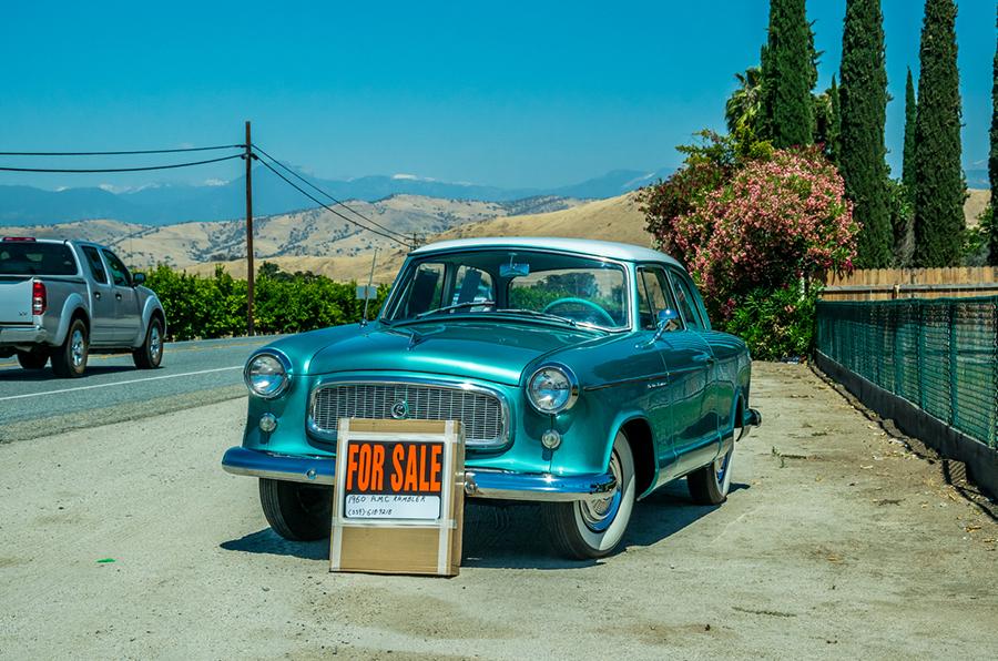 Altes, blaues Auto steht am Strassenrand zum Verkauf.