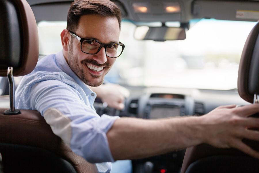 Ein Mann sitzt auf dem Vordersitz eines Autos, dreht sich nach hinten um lächelt smart in die Kamera.