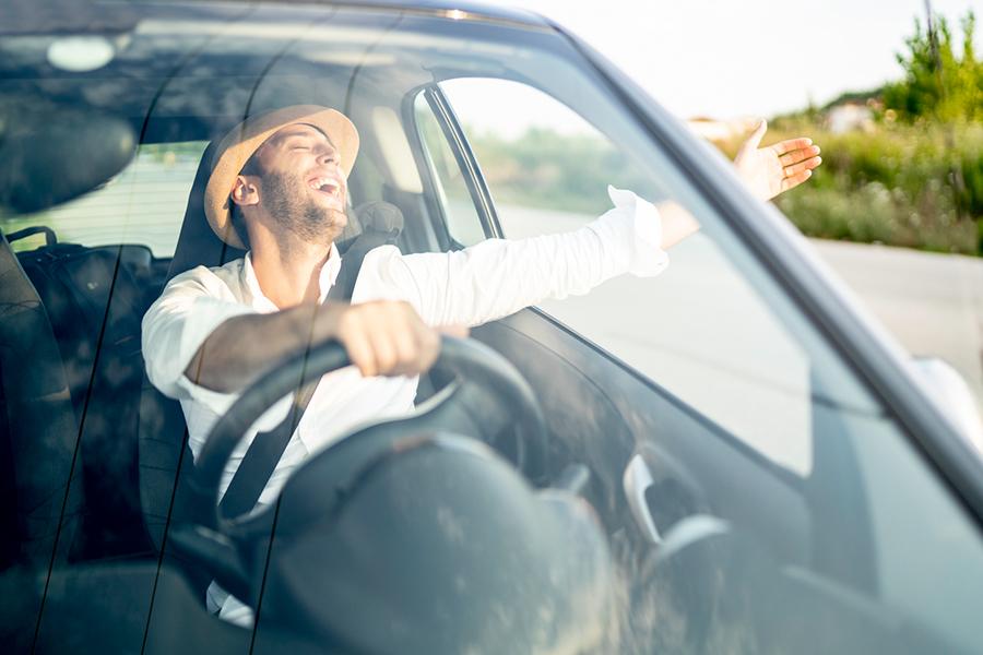 Gut gelaunter Mann streckt seine Hand aus dem Fenster eines fahrenden Autos und singt glücklich zur Musik mit.