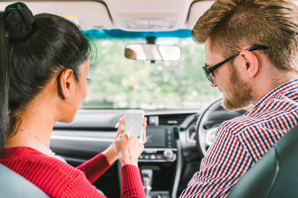 Pendler im Auto mit Smartphone