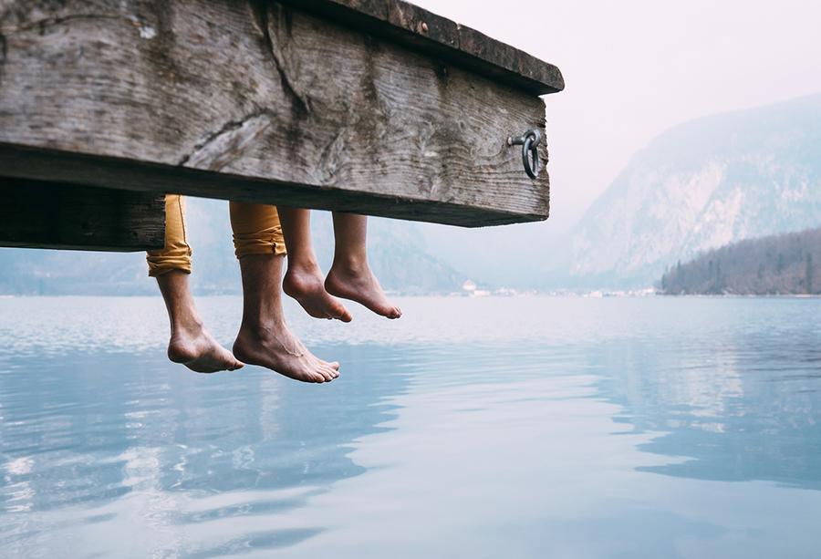 Vater und Sohn schwingen ihre Beine über einen Holzsteg an einem Bergsee