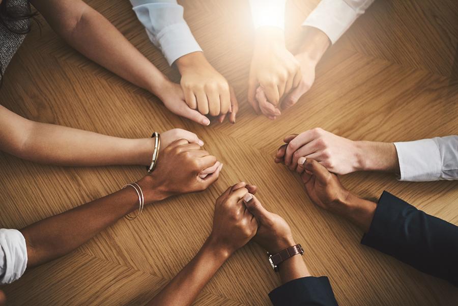 Mehrere Menschen unterschiedlicher Hautfarbe fassen einander die Hände, legen diese auf einen Tisch und bilden damit einen Kreis.