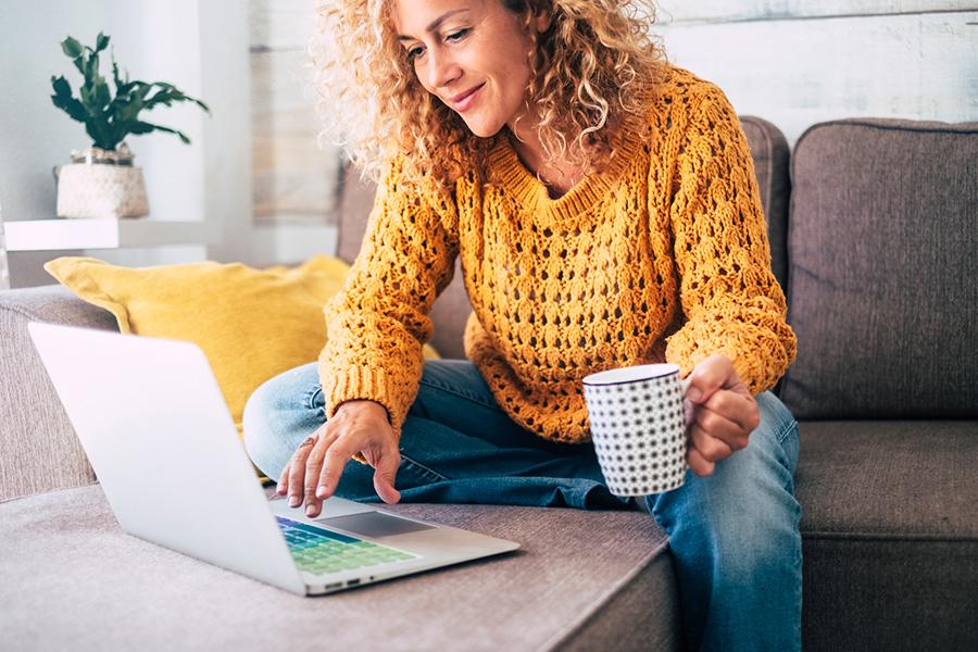 Eine Frau mit gelbem Pulli, Bluejeans und blonden Locken sitzt auf einer grauen Couch vor einem weißen Laptop und hat einen weiß-blau gepunkteten Kaffeebecher in der linken Hand.