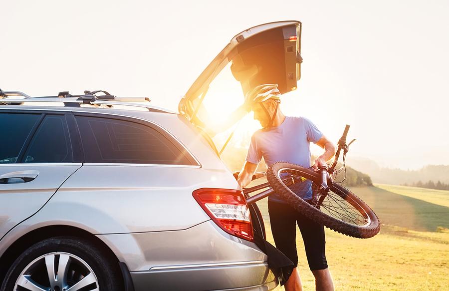 Mann packt Fahrrad in Kofferraum