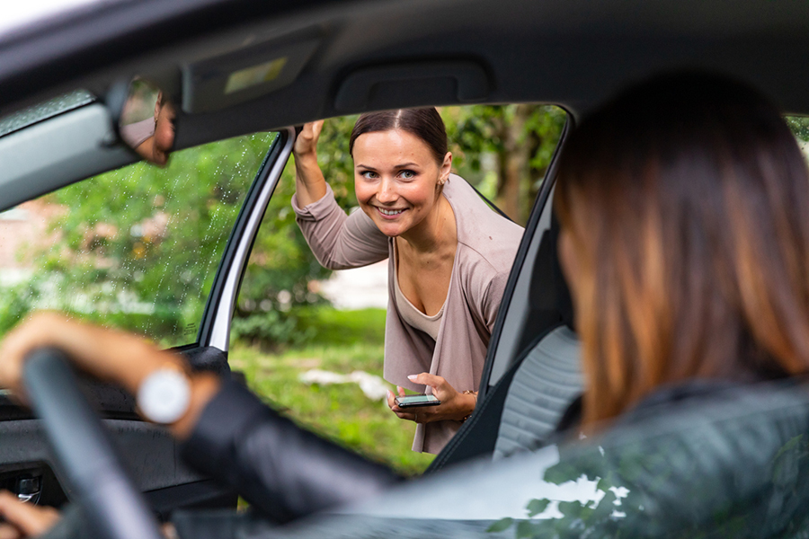 Fahrgemeinschaft: Frau steigt ins Auto ein
