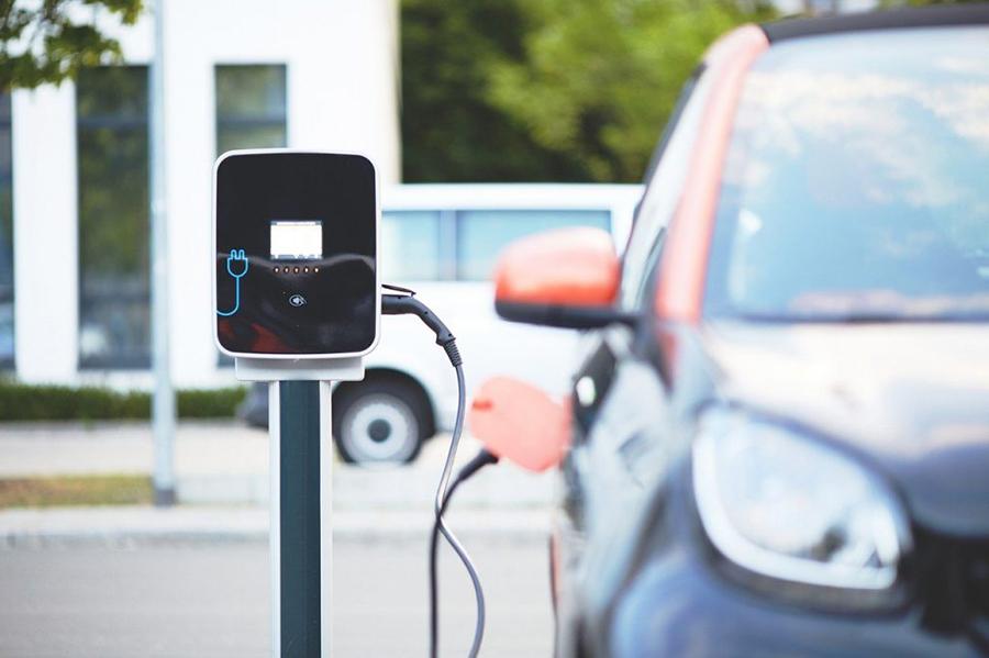 Ein blaues, kleines Elektroauto mit rotem Spiegel steht an einer weiß/schwarzen Ladestation