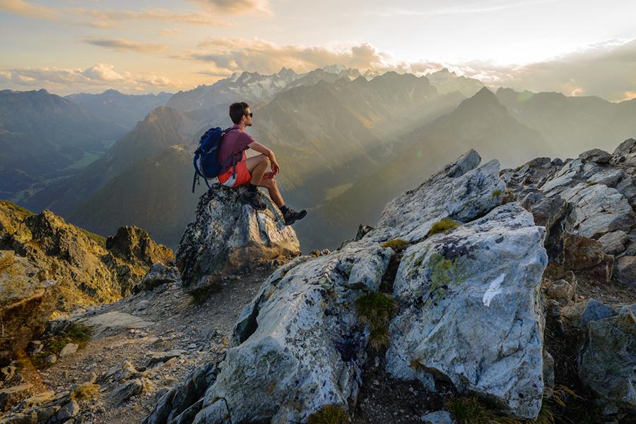 Ein Mann sitzt in kurzer Hose und T-Shirt mit einem Rucksack auf dem Rücken am Rande eines Felsens in den Bergen und geniesst den Sonnenuntergang.