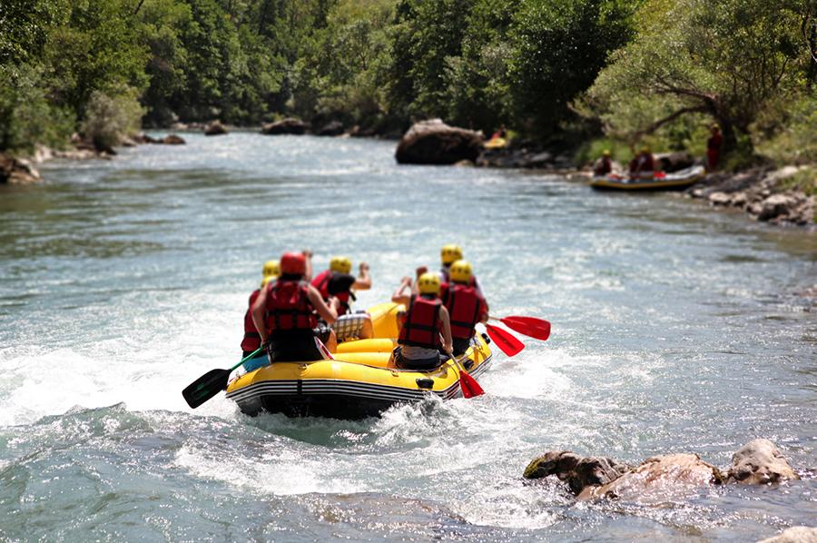 Sechs Menschen sitzen mit Rettungswesten ausgestattet in einem gelben Schlauchboot und raften über einen Fluss.