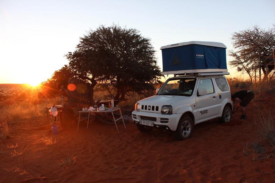 Weißes Auto mit Dachzelt campt bei Sonnenuntergang.