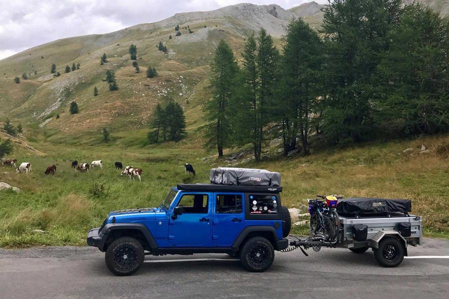 Blauer Geländewagen mit Anhänger und Dachzelt fährt durch Landschaft