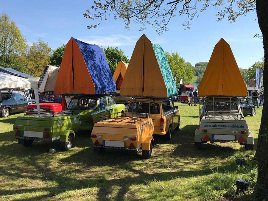 Drei Autos mit aufgestelltem Dachzelt stehen nebeneinander auf der Wiese.