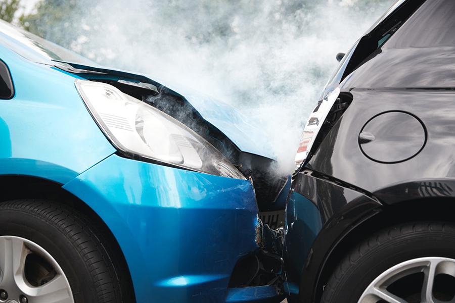 Ein hellblaues Auto ist in den Kofferraum eines schwarzen, kleinen Autos gefahren. Die Motorhaube des blauen Autos ist komplett zerbeult.