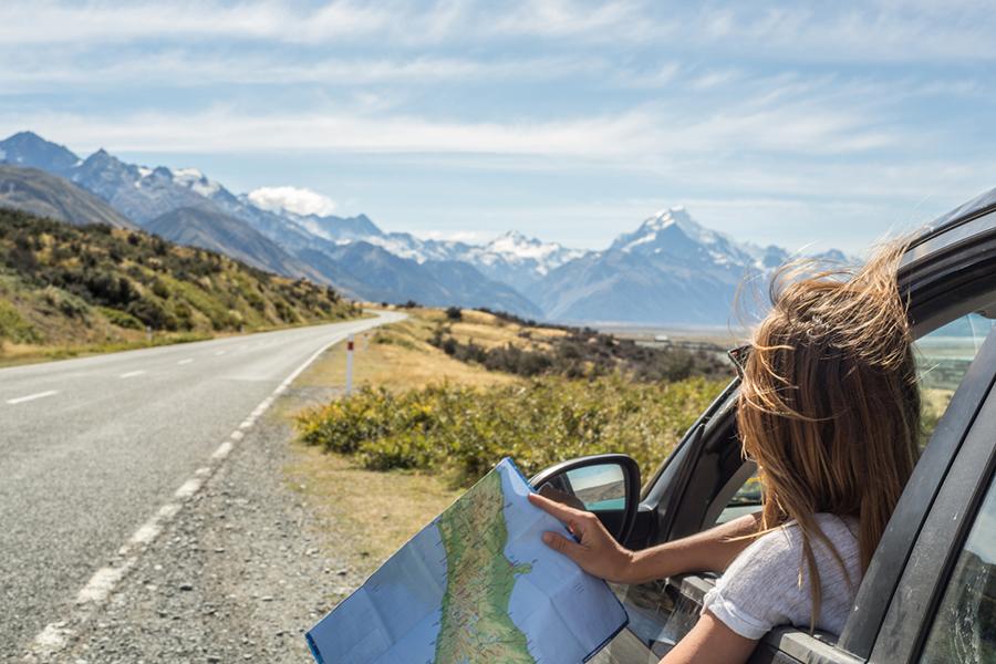 Eine Frau steht mit ihrem Auto bei sonnigem Wetter mit heruntergekurbeltem Fenster am Strassenrand, beugt sich aus dem Auto und hält eine Straßenkarte in den Händen.and