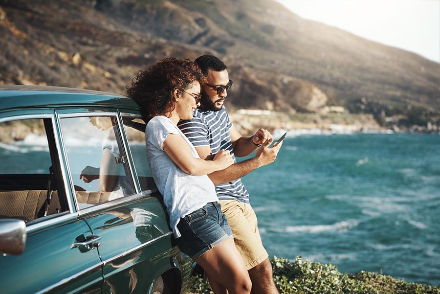 Pärchen lehnt an einem blauen Auto. Sie halten eine Karte in der Hand und befinden sich auf eines Roadtrip ans Meer.