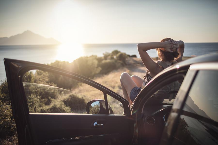 Frau, die auf der Motorhaube ihres Autos sitzt und in die Sonne guckt