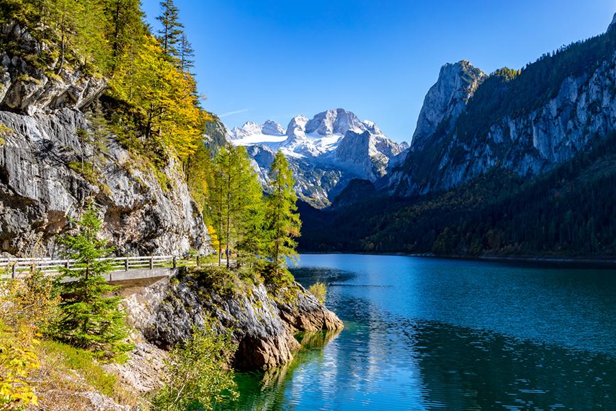Ein Bergsee im Herbst, umgeben von grünen Wäldern