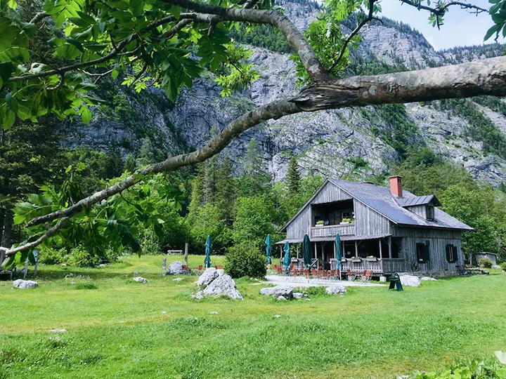 Eine große Berghütte aus Holz, umgeben von Bergen und grünen Wiesen.