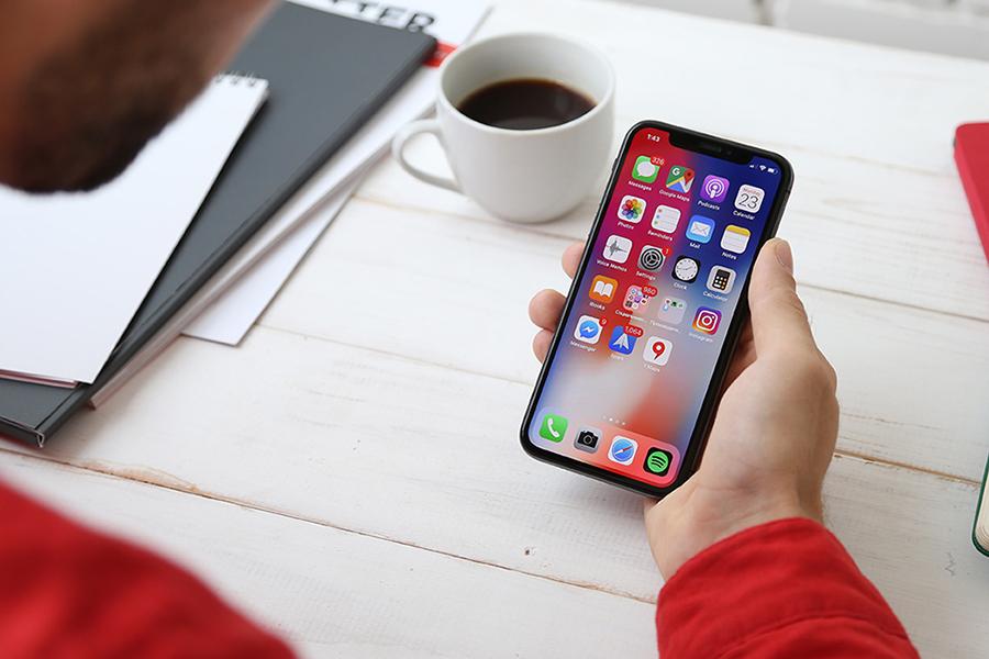 Mann sitzt mit aufgestütztem Ellebogen am Tisch und hält ein Smartphone in der Hand. Auf dem Screen sind verschiedene Apps zu sehen.