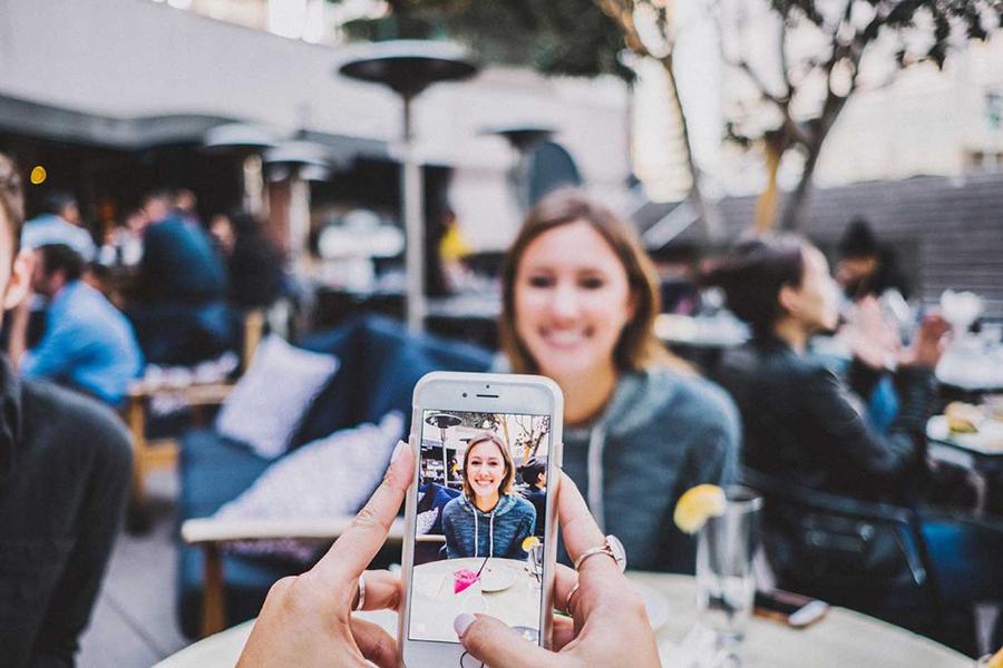 Frau sitzt lächelnd in einem Kaffee und wird mit einem Smartphone fotografiert.