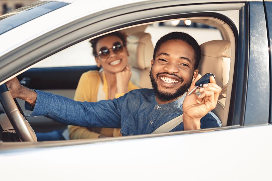 Ein lächelndes afroamerikanisches Pärchen, das im Auto sitzt. Der Mann hält den Autoschlüssel hoch.