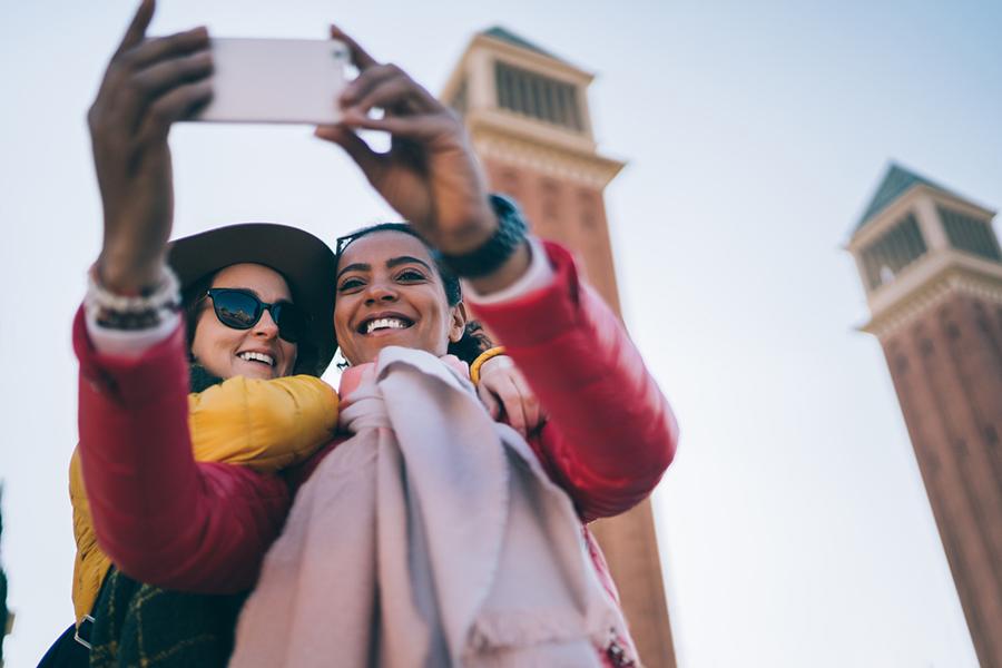 Zwei Freundinnen machen ein Selfie mit dem Smartphone vor einem Wahrzeichen in Barcelona