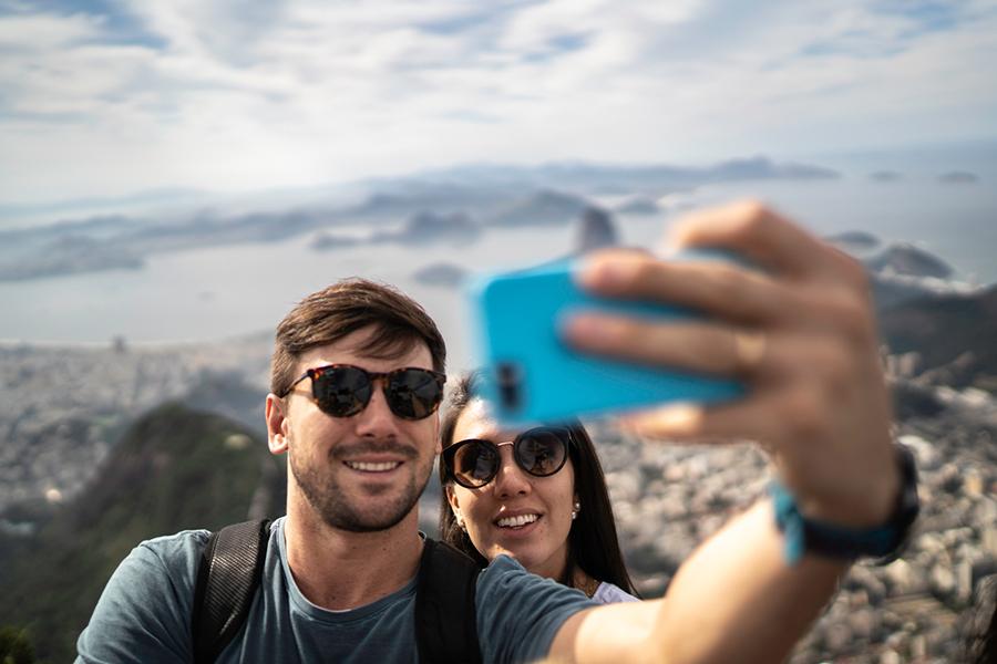 Ein Pärchen mit Sonnenbrillemacht im Sommer ein Selfie mit einem blauen Smartphone. Als Hintergund ist eine Stadt sowie das Meer und Felsen zu sehen.