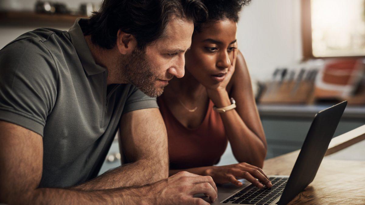 Ein Mann und eine Frau sitzen gemeinsam vor einem Laptop und schauen auf den Screen