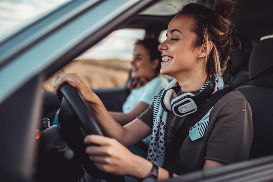 Zwei junge Frauen sitzen an einem Sommertag im Auto und haben gute Laune. Die Fahrerin trägt lässig einen Kopfhörer um den Hals.
