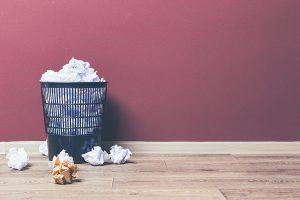 Ein blauer Papierkorb steht vor einer lilafarbenen Wand. Auf dem Boden liegen um den Papierkorb zusätzlich zerknüllte Papiere herum.