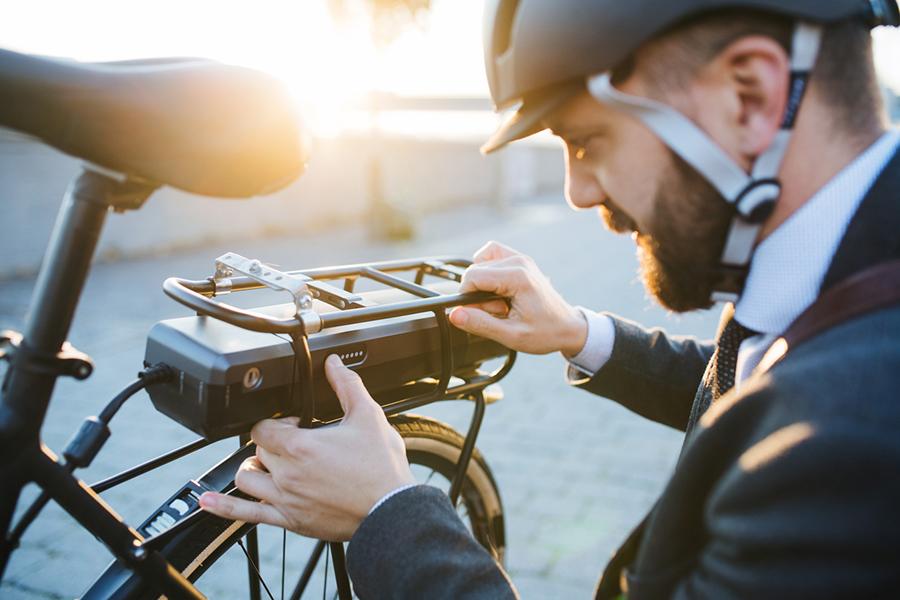 Ein Mann im Anzug und mit Fahrradhelm bekleidet kniet bei Sonnenuntergang vor dem Akku seines E-Bikes