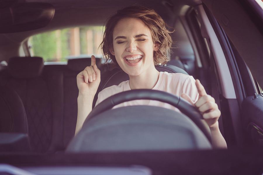 Junge Frau mit braunen Haaren und rosa T-Shirt sitzt gut gelaunt hinter dem Steuer im Auto.