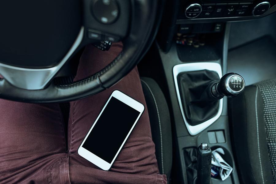Auf dem Schoss des Fahrers liegt ein weißes Smartphone. Das Thema hier ist: WLAN im Auto.