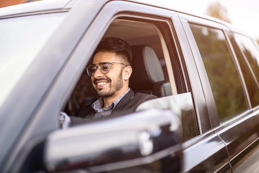 Junger Mann mit Brille sitzt lächelnd hinterm Steuer seines Autos