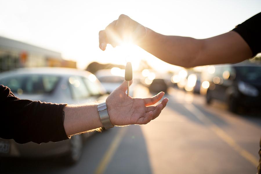 Zwei Hände die sich einen Autoschlüssel übergeben