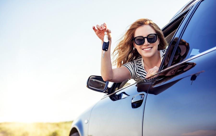 Lächelnde Frau mit Sonnenbrille lehnt sich aus dem Autofenster und hält einen Autoschlüssel in den Händen.