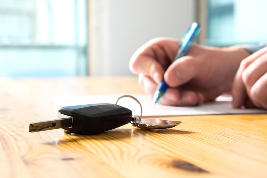 Nahaufnahme - Auf dem Tisch liegt ein Autoschlüssel - Im Hintergrund sieht man die Hand einer Person ein Papier unterschreiben