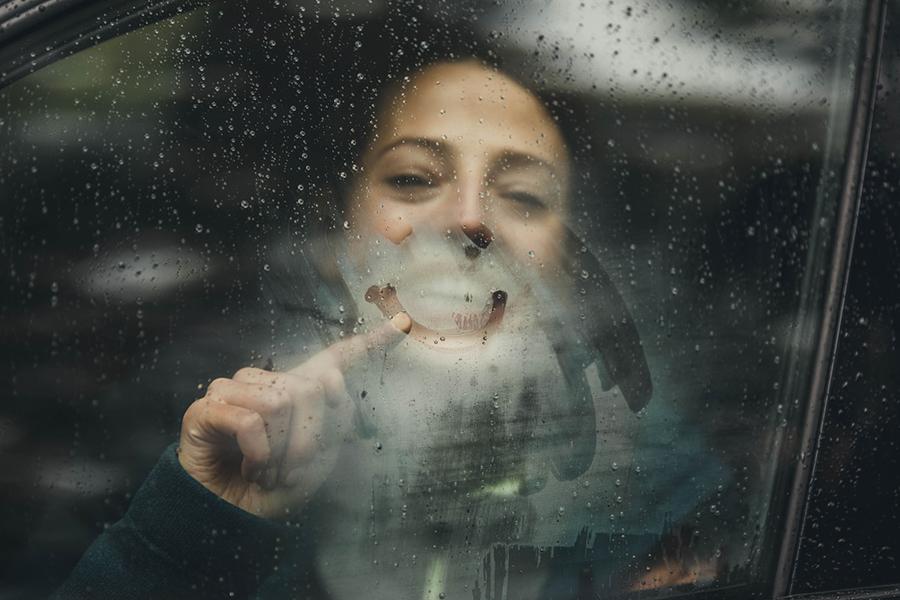 Lächelnde Frau sitzt im Auto direkt hinter der beschlagenen Scheibe und malt einen lächelnden Mund mit dem Finger auf die Scheibe.