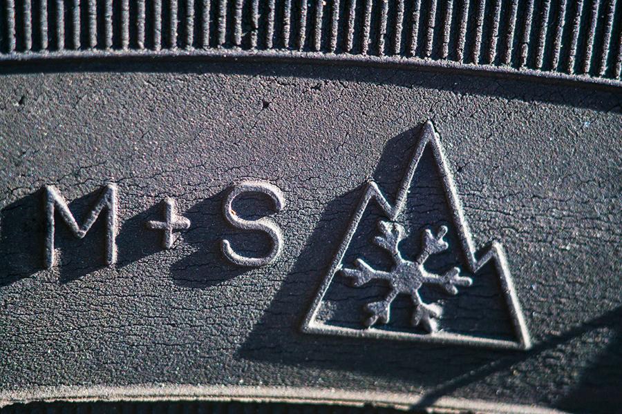 Nahaufnahme eines Reifens - die zwei Symbole für wintertaugliche Reifen sind sichtbar.