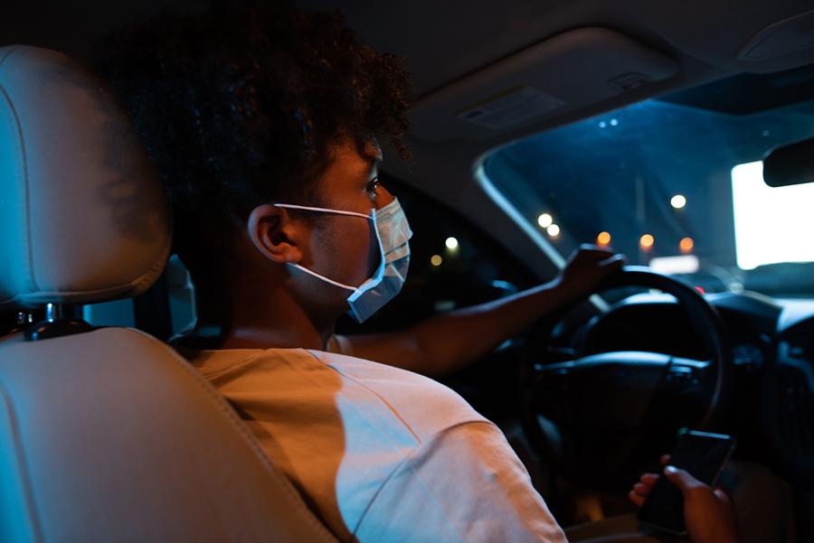 Junger Mann sitzt im Autokino hinterm Steuer und trägt Maske