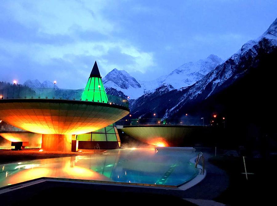 Blick auf ein Schwimmbecken inmitten von schneebedeckten Bergen, zwei angeleuchtete Gebäude des Schwimmbads