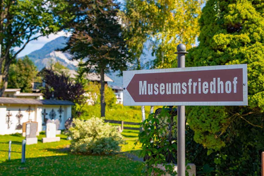 """Straßenschild auf dem """"Museumsfriedhof"""" steht, Natur und ein weißes Haus im Hintergrund"""