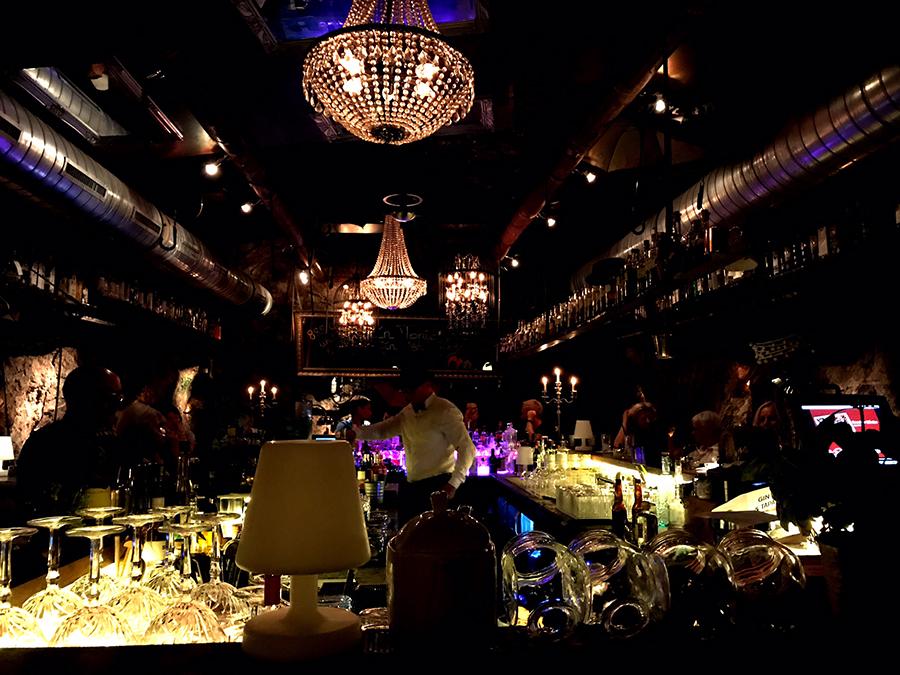 Blick in eine Bar mit Barkeeper, Lichtern und Cocktailgläsern