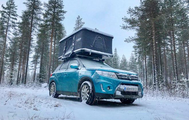 Blaues Auto mit Dachzelt im Schnee