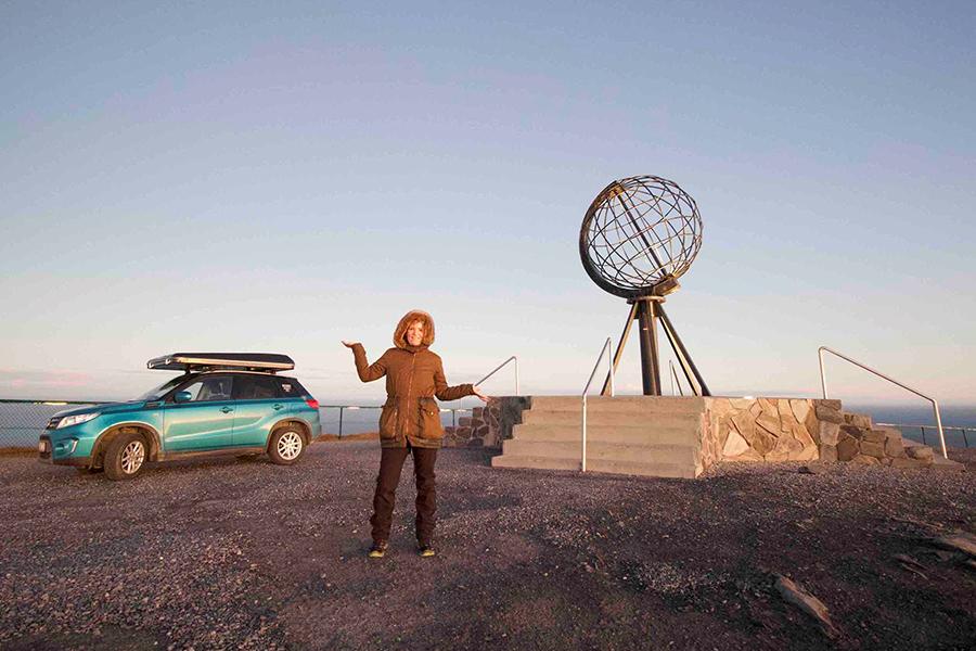 Rebecca Roß und ihr Auto mit Dachzelt im Hintergrund