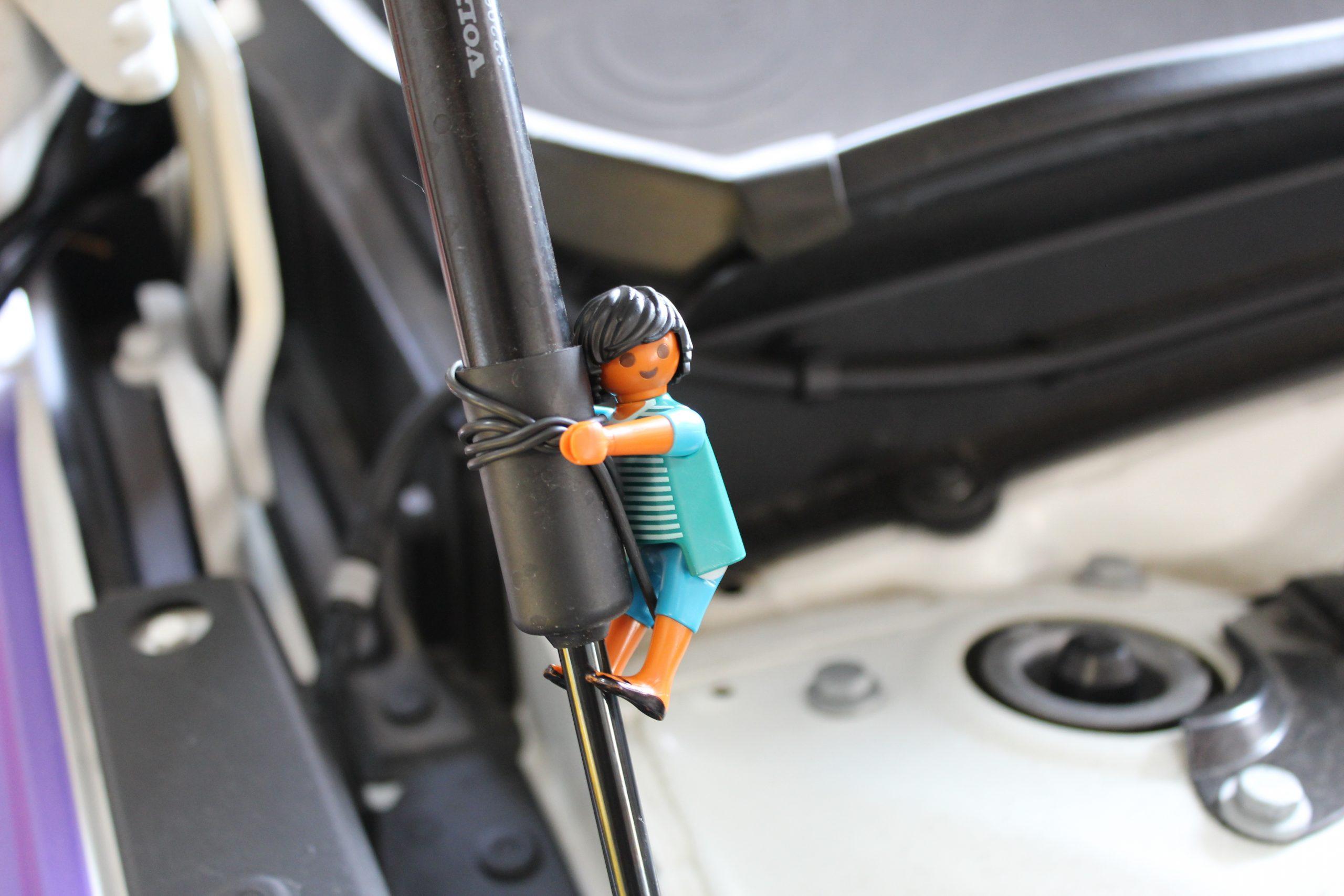 Playmobilmännchen klettert die Motorhaube hoch