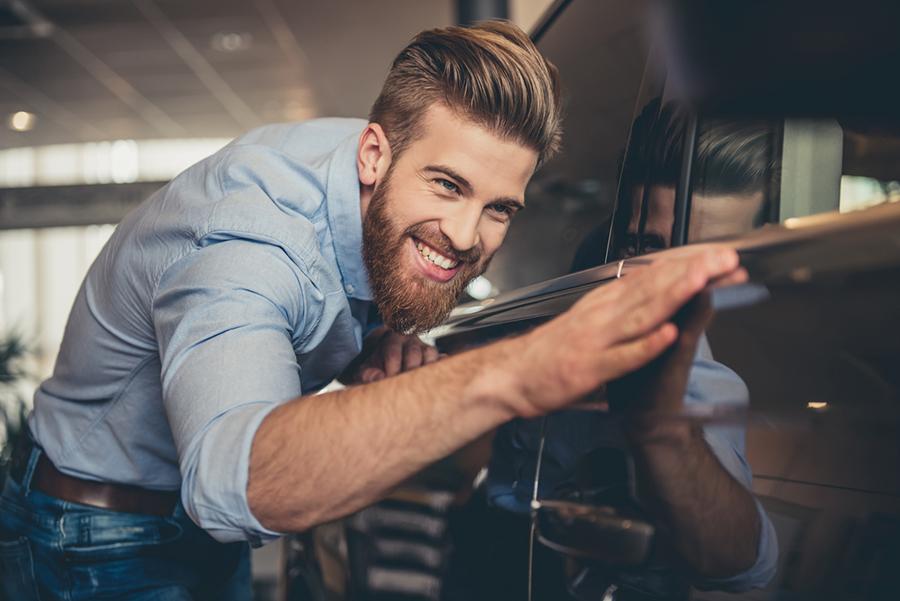 Junger Mann streicht über sein Auto und lächelt