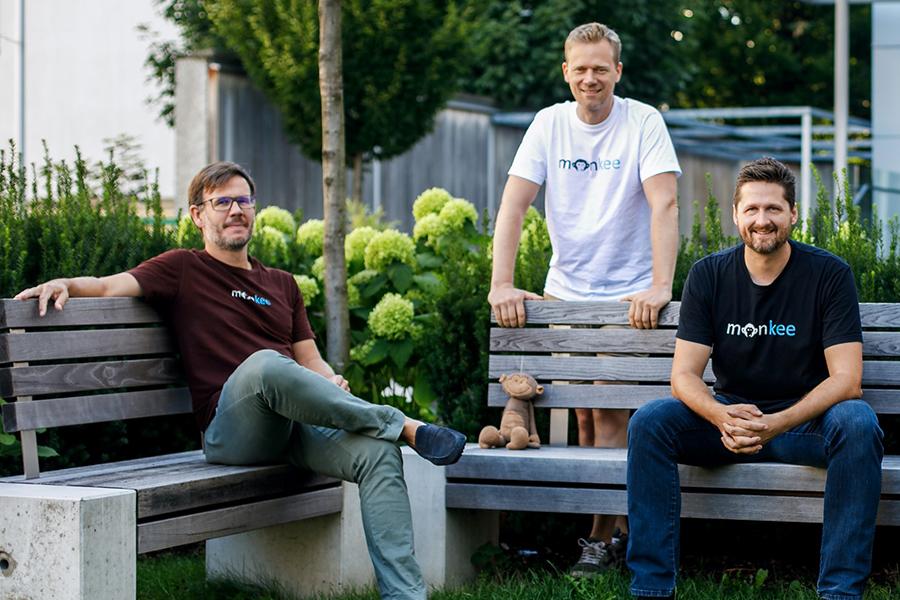 Gruppenbild der drei Gründer der App Monkee. Zwei sitzen auf Holzbänken, einer steht mittig dahinter